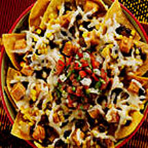 Nachos loaded with muenster cheese, fresh corn kernels, diced green ...